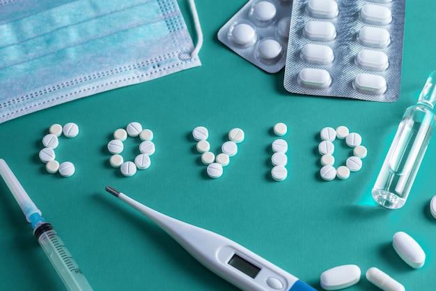 Płaskie ułożenie kształtu pigułek lekarskich jako słowo covid 19 ze strzykawką, termometrem i tabletkami na niebieskim tle, koncepcja opieki zdrowotnej i zapobieganie rozprzestrzenianiu się pandemii covid-19, koronawirusa