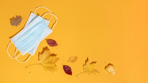 Płaskie ułożenie masek medycznych z jesiennymi liśćmi i miejscem na kopię