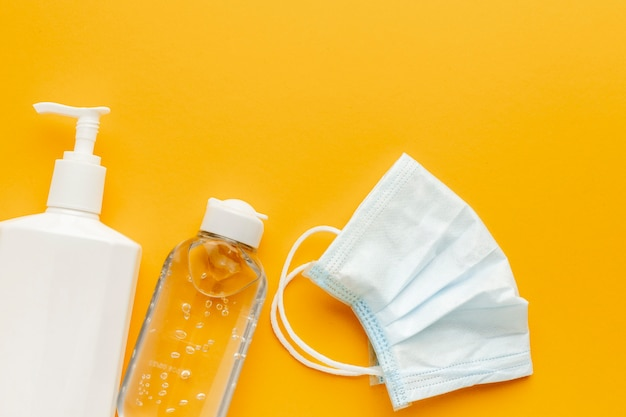 Płaskie ułożenie maski medycznej z butelką z płynem i środkiem odkażającym do rąk