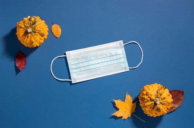 Płaskie ułożenie maski medycznej z jesiennymi liśćmi