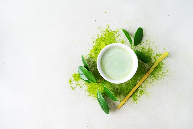 Płaskie ułożenie miski ekologicznej zielonej herbaty matcha w proszku z łyżką chashaku