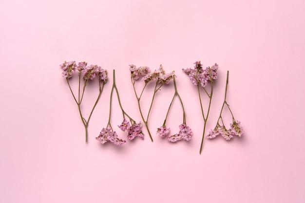 Płaskie ułożenie naturalnych kwiatów polnych na delikatnym różu.