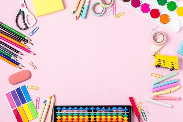 Płaskie ułożenie nowoczesnego różowego pulpitu biurowego z przyborami szkolnymi na stole wokół pustej przestrzeni na tekst na górze