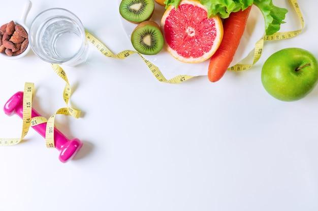 Płaskie ułożenie owoców, warzyw, hantli, miarki i szklanki wody na białym stole
