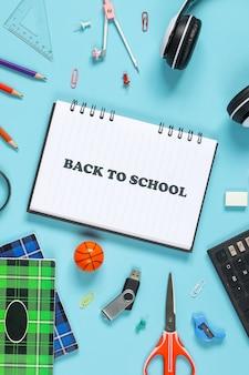 Płaskie ułożenie papeterii dla koncepcji powrotu do szkoły na niebieskim tle