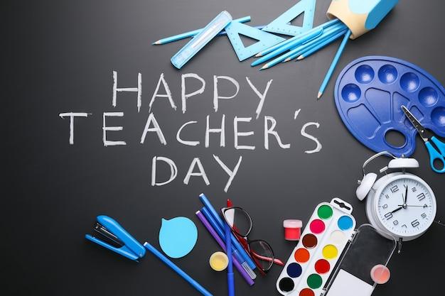 Płaskie ułożenie papeterii szkolnej i napisu szczęśliwego dnia nauczyciela w ciemności