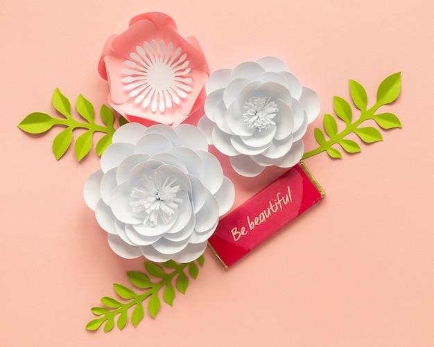 Płaskie ułożenie papierowych kwiatów z liśćmi na dzień kobiet