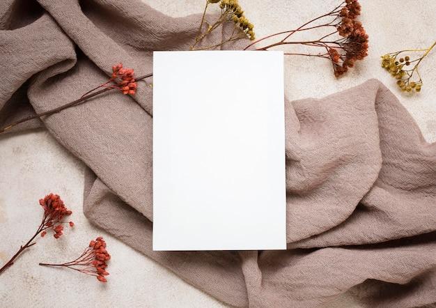 Płaskie ułożenie papieru z jesienną rośliną i tkaniną
