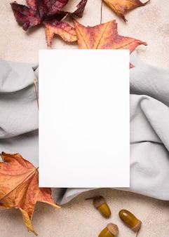 Płaskie ułożenie papieru z tkaniną i jesiennymi liśćmi