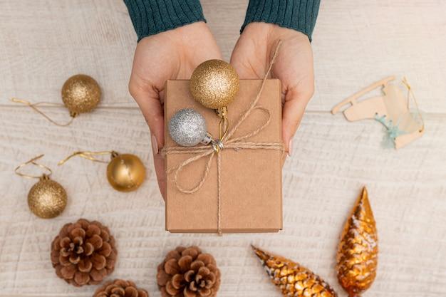 Płaskie ułożenie prezentu bożonarodzeniowego w dłoniach kobiety, kulki dekoracji i stożki leżące na stole.