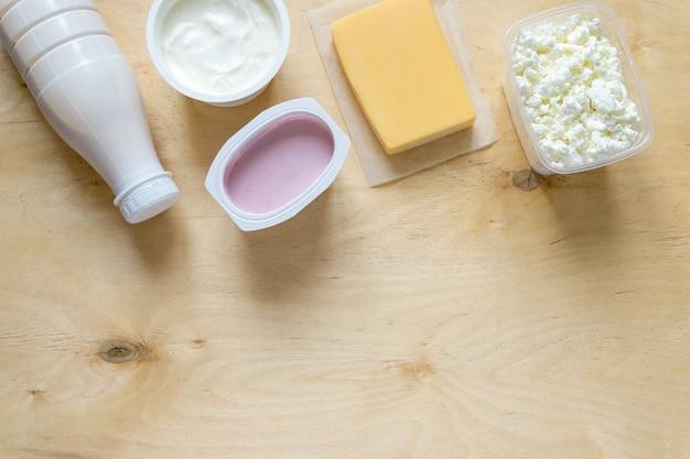Płaskie ułożenie produktów mlecznych na drewnianym tle widok z góry z miejscem na kopię