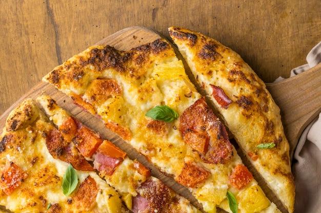 Płaskie ułożenie pysznej pieczonej pizzy z ananasem i papają
