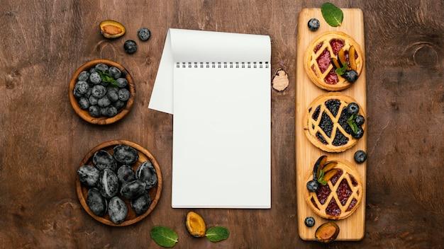 Płaskie ułożenie pysznych ciast owocowych ze śliwkami i notesem