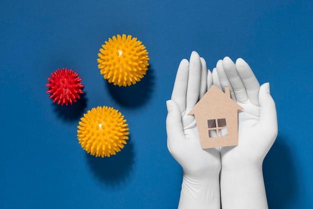 Płaskie ułożenie rąk z rękawiczkami trzymającymi i chroniącymi dom przed wirusami