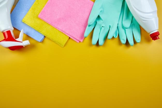 Płaskie ułożenie różnych produktów do czyszczenia domu na żółtym stole