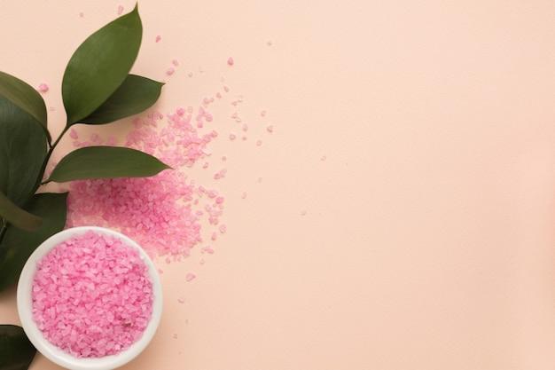 Płaskie ułożenie różowej soli do kąpieli rozrzuconej wokół miski i zielonych liści na tle koloru brzoskwini