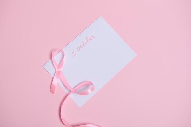 Płaskie ułożenie różowej wstążki z niekończącym się końcem leżącej na białej kartce papieru z zaśmiecaniem 1 października, międzynarodowy symbol miesiąca świadomości raka piersi. opieka zdrowotna i koncepcja medyczna kobiety