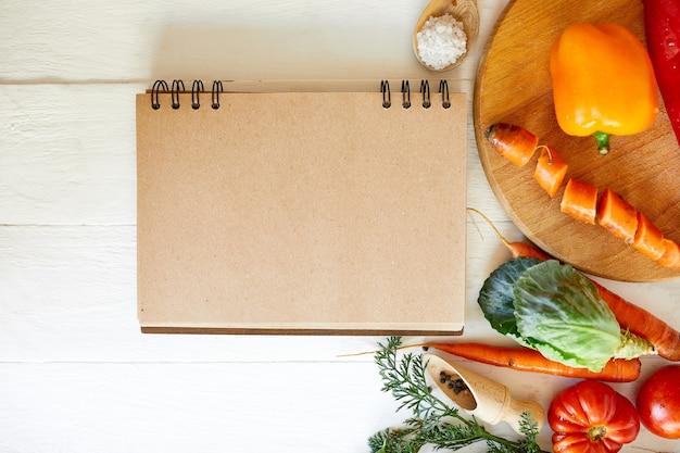 Płaskie ułożenie składnika gotowania, warzyw wokół książki kucharskiej, sklep spożywczy, lokalne jedzenie, zdrowe, czyste odżywianie, jedzenie wegetariańskie i wegańskie, koncepcja wiosny diety, widok z góry, miejsce.