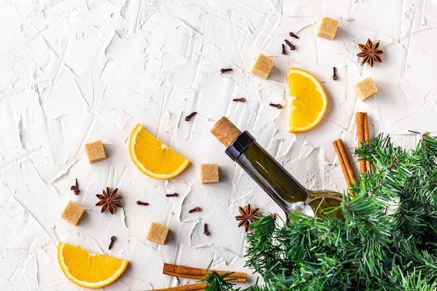Płaskie ułożenie składników na grzane wino. butelka wina, pomarańczy, cukru, lasek cynamonu, anyżu i gałązek jodły. widok z góry z miejscem na kopię