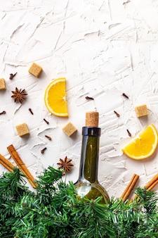 Płaskie ułożenie składników na grzane wino. przepis na świąteczny napój rozgrzewający. butelka wina, pomarańczy, cukru, lasek cynamonu, anyżu i gałązek jodły. widok z góry z miejscem na kopię