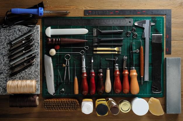 Płaskie ułożenie skórzanych narzędzi roboczych na drewnianym biurku