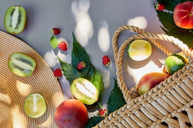 Płaskie ułożenie słomkowego kapelusza i torby z owocami malina, brzoskwinia, kiwi, limonka na szarej powierzchni w słońcu, czas letni. koncepcja spożywczy, miejsce, widok z góry.