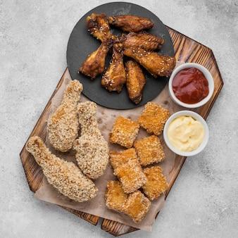 Płaskie ułożenie smażonego kurczaka i bryłek z różnymi sosami