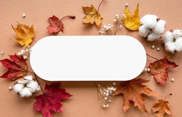 Płaskie ułożenie suszonych liści i pusty transparent na beżowym tle