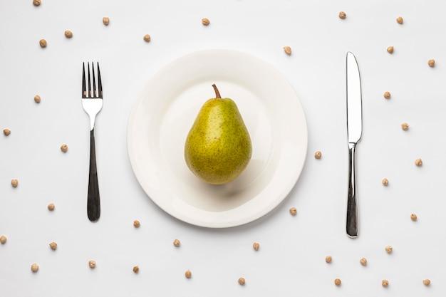 Płaskie ułożenie świeżej gruszki na talerzu ze sztućcami