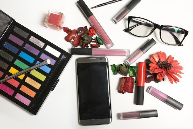 Płaskie ułożenie szminki, błyszczyka, okularów i telefonu komórkowego na białym tle