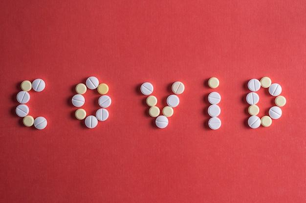 Płaskie ułożenie tabletek leku w kształcie słowa covid 19, koncepcja opieki zdrowotnej i zapobieganie rozprzestrzenianiu się pandemii covid-19, koronawirusa