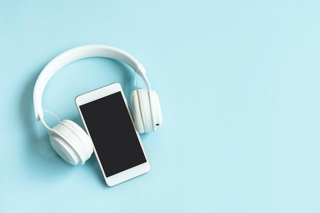 Płaskie ułożenie telefonu komórkowego i słuchawek bezprzewodowych na niebieskim tle. widok z góry i kopia miejsca
