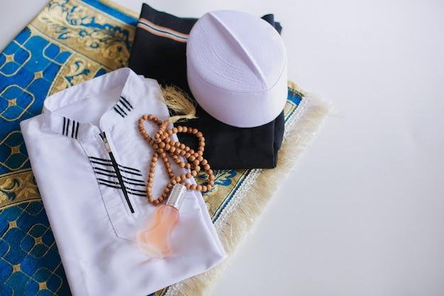 Płaskie ułożenie tradycyjnego stroju muzułmańskiego i koralików modlitewnych na macie modlitewnej z miejscem na kopię