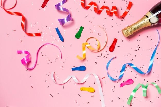 Płaskie ułożenie uroczystości. butelka szampana z kolorowymi serpentynami na różowym tle.