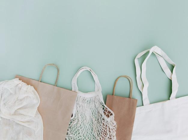 Płaskie ułożenie z ekologicznymi białymi papierowymi torbami i siatkami na zielonym tle z miejscem na kopię