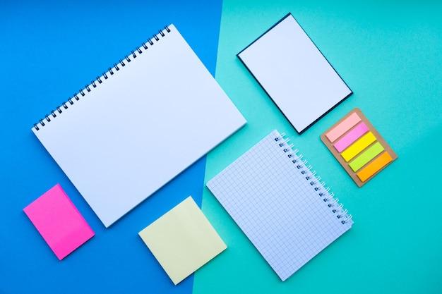 Płaskie ułożenie ze spiralną naklejką na notatnik i artykułami biurowymi na niebieskim tle z powrotem do szkoły