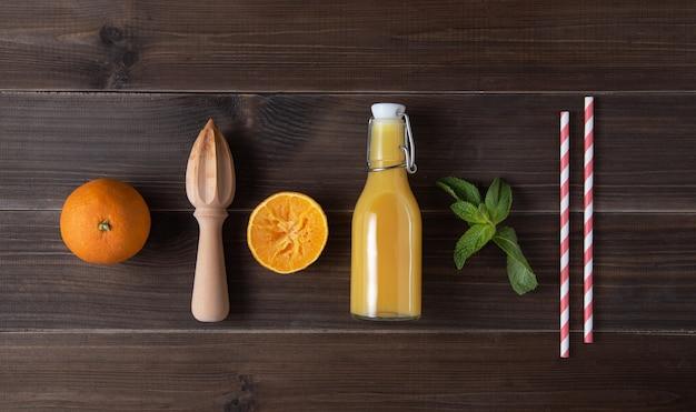 Płaskie ułożenie ze świeżym sokiem pomarańczowym wyciskacz do mięty cytrusowej na drewnianym tle