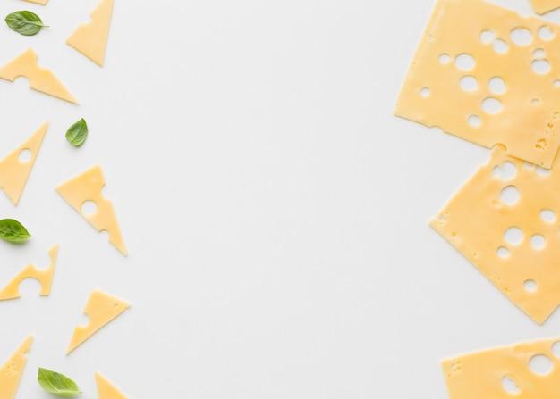 Płaskie ułożone trójkątne i kwadratowe plastry sera ementalowego z miejscami do kopiowania