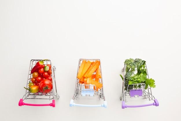 Płaskie wózki sklepowe z pysznymi warzywami