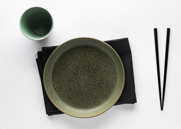 Płaskie zastawy stołowe z pałeczkami i serwetką