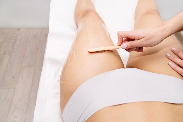 Płaskie zdjęcie krótkiej dłoni kosmetyczki wykonującej zabieg woskowania kobiety na udzie