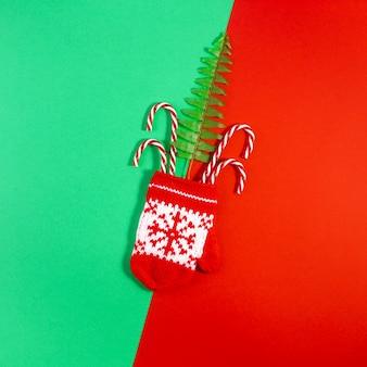 Płaskie zdjęcie leżące z ozdób choinkowych na geometrycznej czerwieni i zieleni