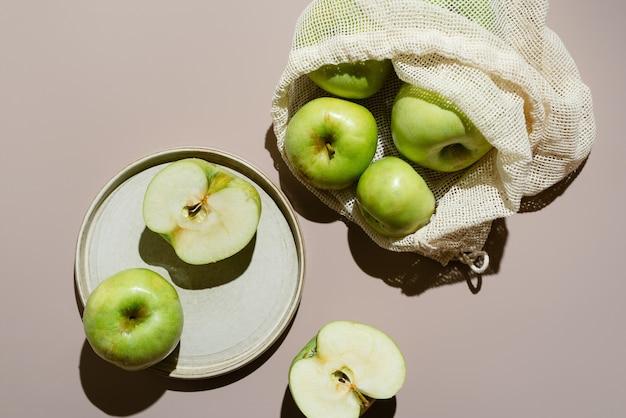 Płaskie zielone jabłka organiczne w bawełnianej siateczkowej torbie z wyciętą połówką na szarym talerzu