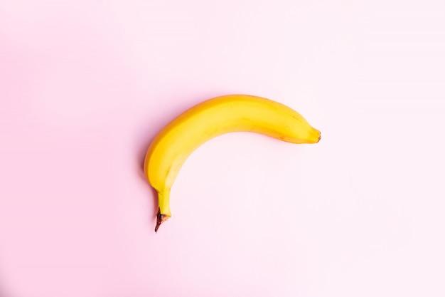 Płaskiego składu słodki banan na różowym tle z kopii przestrzenią dla twój teksta.