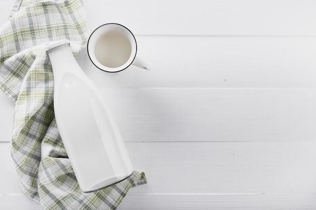 Płasko leżąca butelka mleka z filiżanką na stole