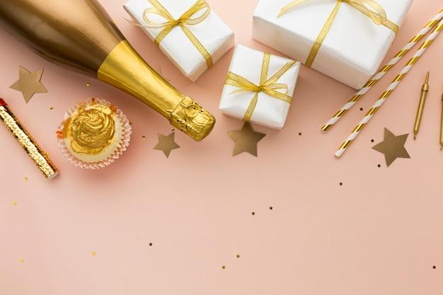 Płasko leżąca butelka szampana z prezentami