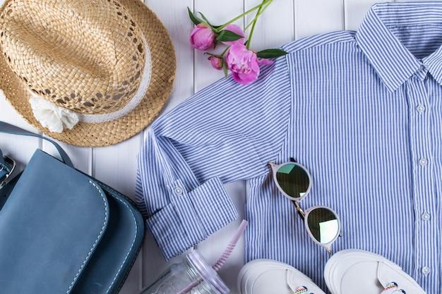 Płasko leżąca kobieta letnie ubrania i akcesoria kolaż na białym z koszulą, dżinsami, okularami, butami, torebką, kapeluszem, słoikiem