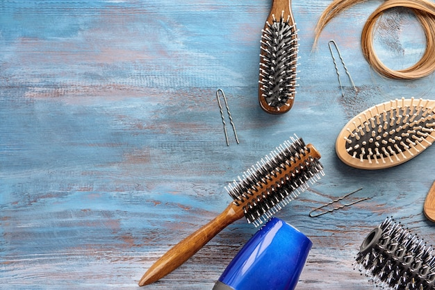 Płasko leżąca kompozycja z narzędziami fryzjerskimi i kosmykiem blond włosów na drewnianym