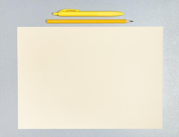 Płasko leżąca kompozycja żółtego długopisu, ołówka i kartki żółtego papieru na szarej powierzchni