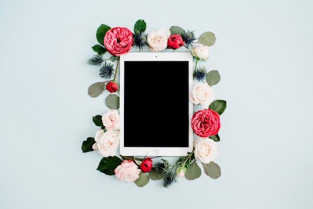 Płasko leżąca kwiatowa ramka z tabletką, czerwonymi i beżowymi pąkami kwiatów róży na bladym, pastelowym niebieskim kolorze